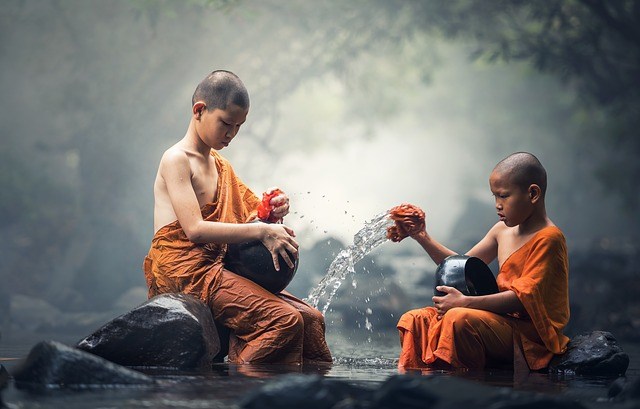 two monk initiates washing dishes in river