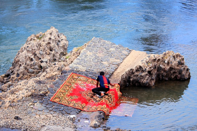 man cleaning carpet at river