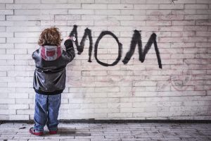 kid writing mom on wall